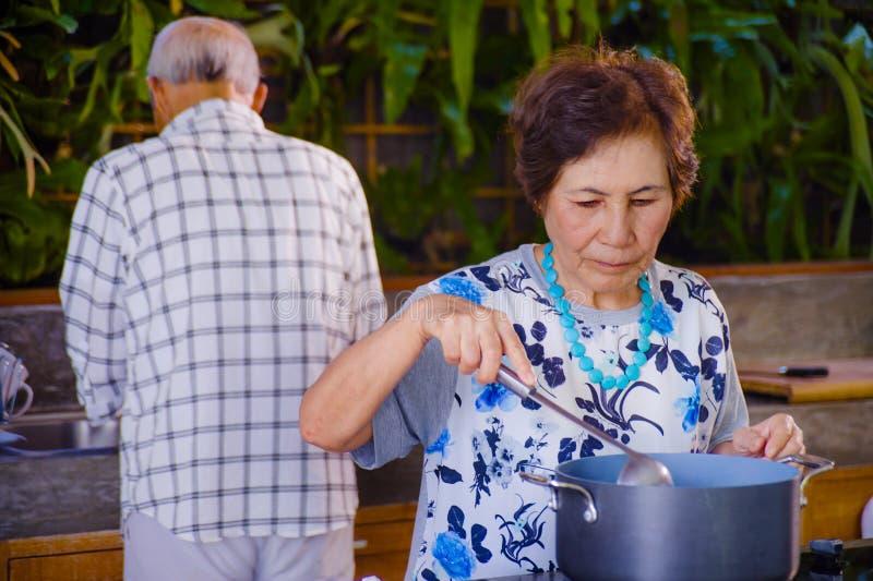 Höga lyckliga och härliga pensionerade asiatiska japanska par som tillsammans lagar mat hemmastatt kök som tycker om förbereda må royaltyfri fotografi