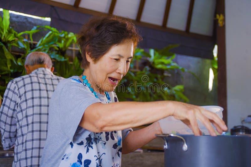 Höga lyckliga och härliga pensionerade asiatiska japanska par som tillsammans lagar mat hemmastatt kök som tycker om förbereda må arkivfoto