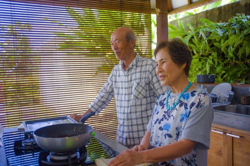 Höga lyckliga och härliga pensionerade asiatiska japanska par som tillsammans lagar mat hemmastatt kök som tycker om förbereda må arkivfoton