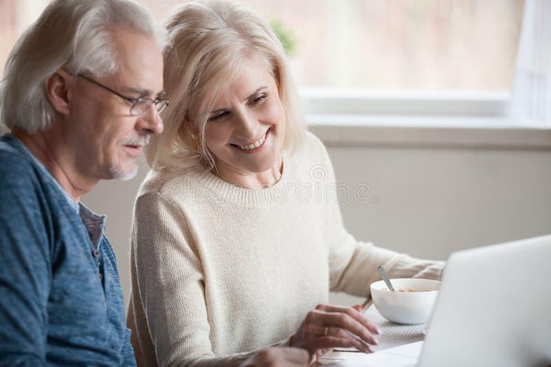 Höga lyckliga par som tycker om genom att använda bärbara datorn som äter frukosttoget royaltyfria bilder
