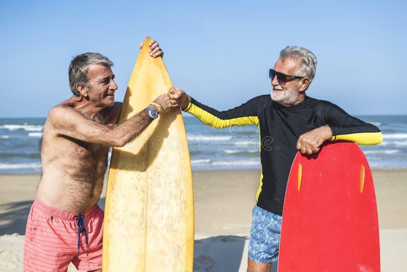 Höga män med surfingbrädor royaltyfria bilder