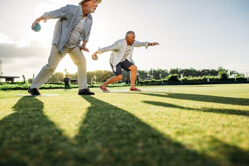 Höga män som spelar boules i en gräsmatta royaltyfri bild