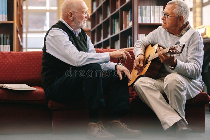 Höga män som spelar gitarren arkivfoto