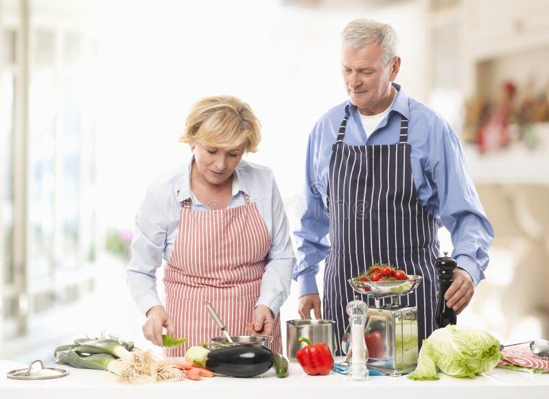 Pensionären kopplar ihop matlagning i kök fotografering för bildbyråer