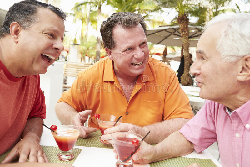 Höga manliga vänner som tillsammans tycker om coctailar i stång royaltyfria bilder