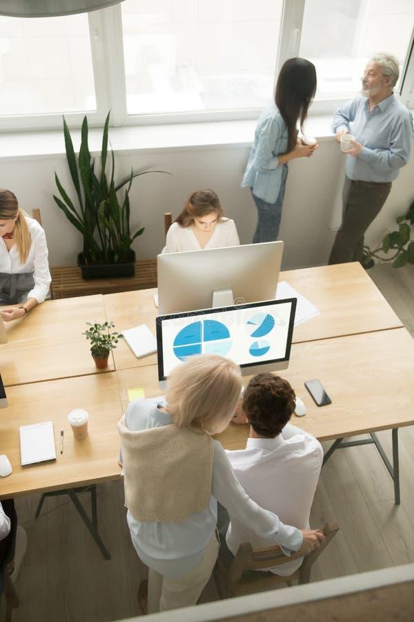 Höga och unga anställda som i regeringsställning arbetar, bästa vertikal sikt royaltyfri fotografi