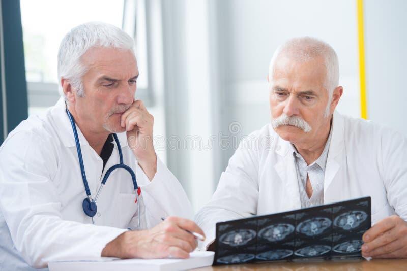 Höga olyckliga doktorer som ser röntgenstrålefotoet arkivbilder