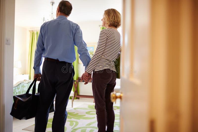 Höga par går in till hotellruminnehavhänder, baksidasikt arkivbild