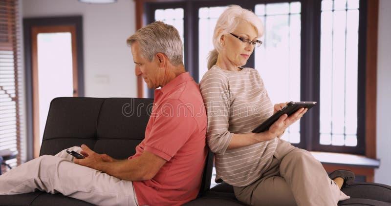 Höga par genom att använda apparater på soffan hemma arkivbild