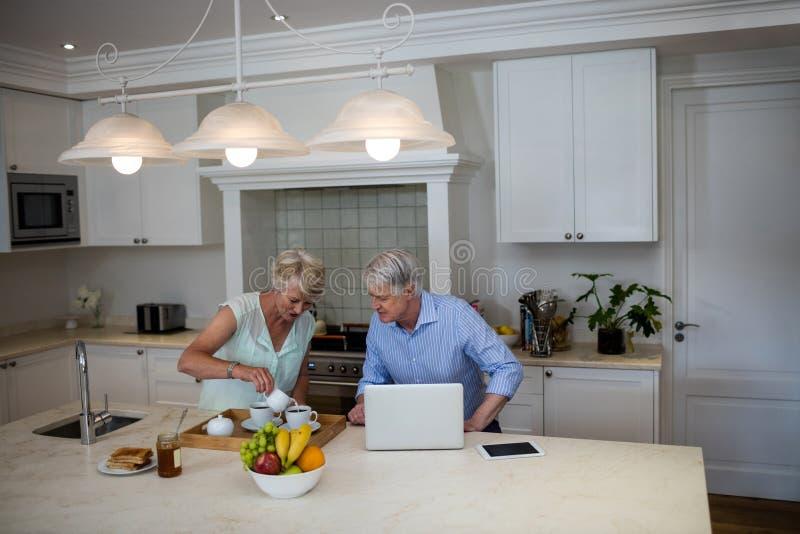 Höga par genom att använda bärbara datorn, medan ha te i kök arkivbild