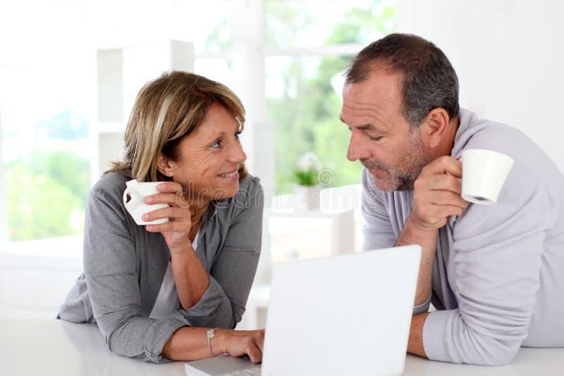 Höga par genom att använda bärbara datorn och dricka kaffe royaltyfria foton