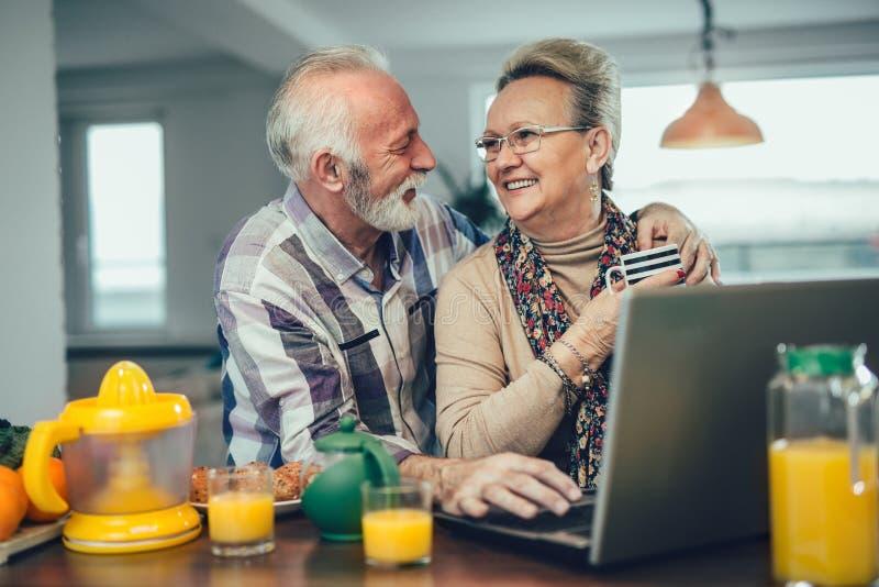 Höga par genom att använda bärbara datorn tillsammans hemma arkivfoto