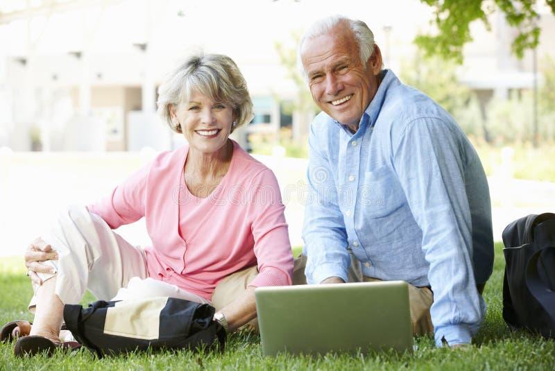 Höga par genom att använda bärbara datorn utomhus arkivfoto