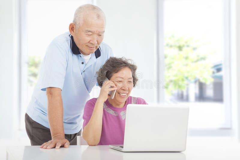 Höga par genom att använda en bärbar dator och en mobiltelefon royaltyfria foton