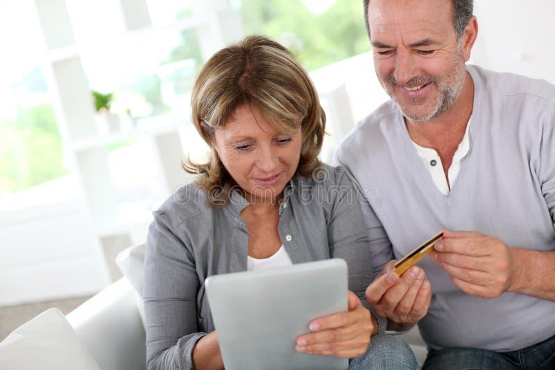 Höga par genom att använda krediteringsbilen som gör online-shopping arkivbilder