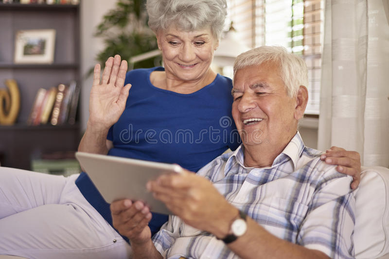 Höga par genom att använda minnestavlan arkivfoto