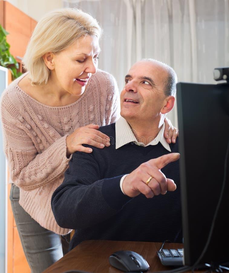 Höga par genom att använda PC hemma royaltyfri fotografi