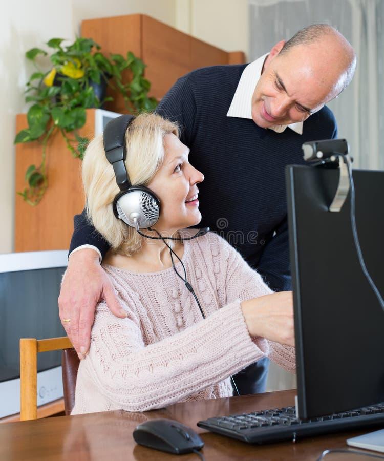 Höga par genom att använda PC hemma arkivfoton