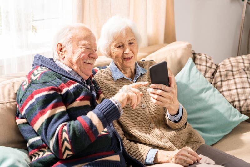 Höga par genom att använda Smartphone inomhus royaltyfria bilder