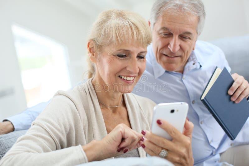 Höga par genom att använda smartphonen hemma arkivfoto