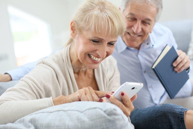 Höga par genom att använda smartphonen och att skratta royaltyfria foton