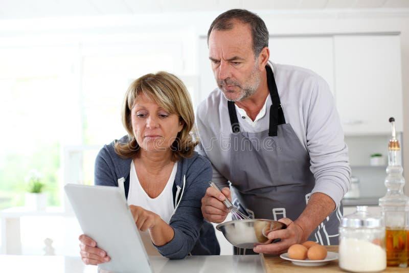 Höga par i köket som förbereder bakelser arkivfoto