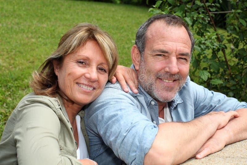 Höga par i koppla av för hemträdgård royaltyfri bild