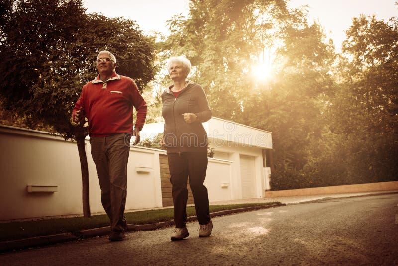 Höga par i sportar som beklär att köra tillsammans på roa arkivfoto