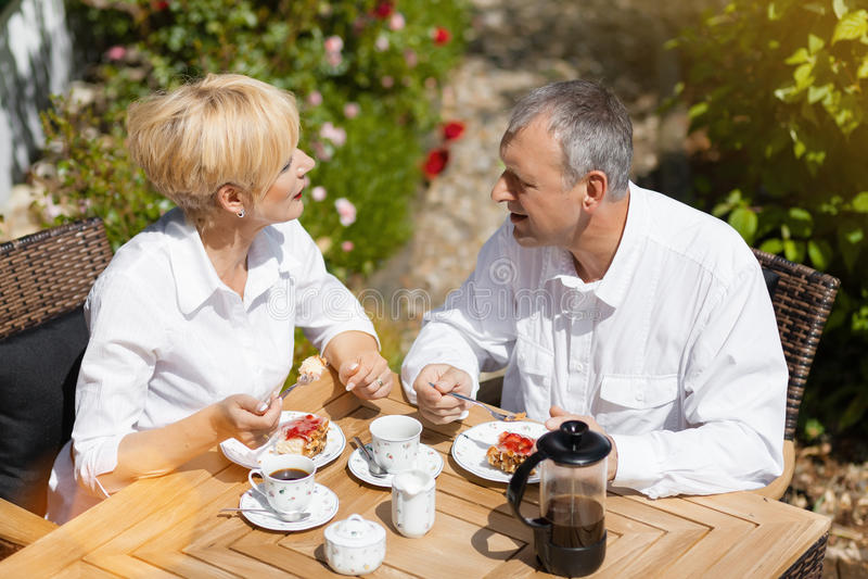 Höga par i trädgård med kaffe royaltyfria foton