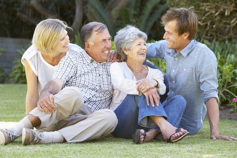 Höga par i trädgård med vuxna barn arkivbild