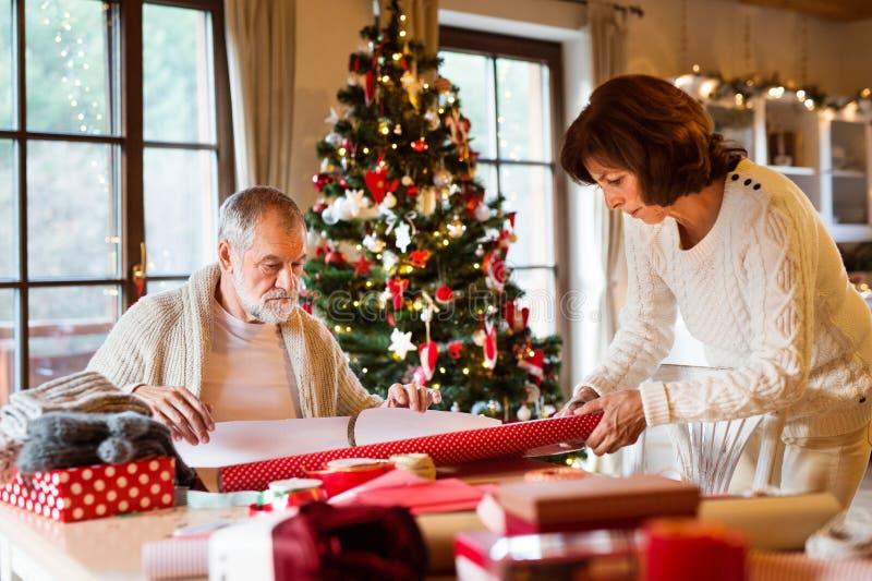 Höga par i tröjor som tillsammans slår in julgåvor fotografering för bildbyråer