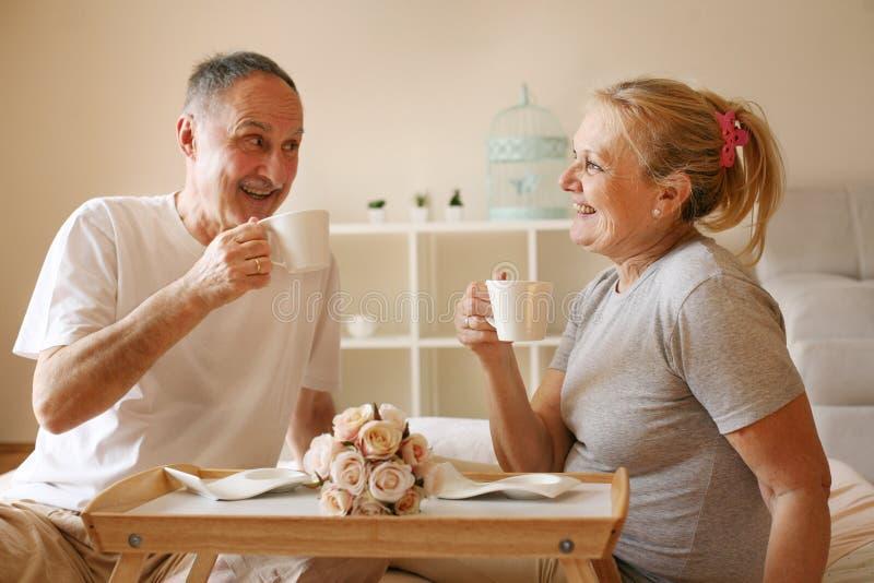 Höga par i underlag Högt folk som dricker kaffe i säng royaltyfria foton