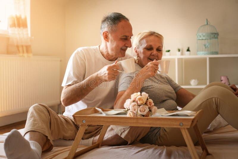 Höga par i underlag Högt folk som dricker kaffe i säng royaltyfri bild