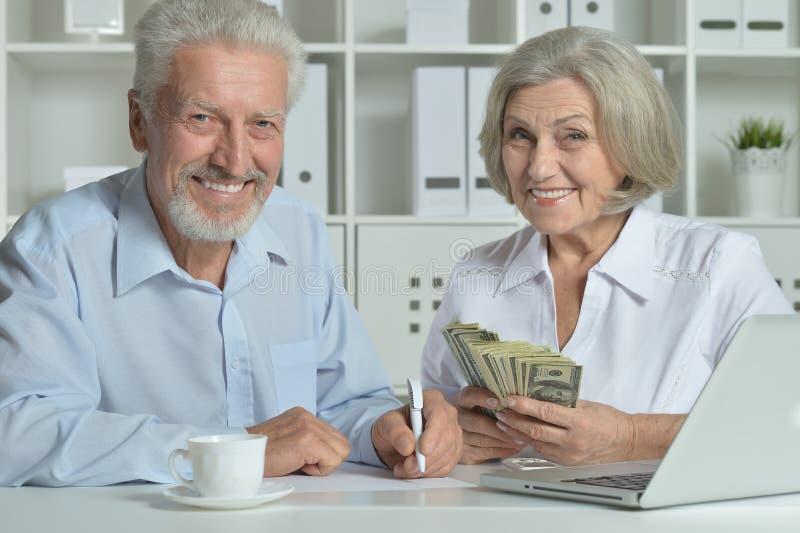 Höga par med bärbara datorn och pengar arkivbilder