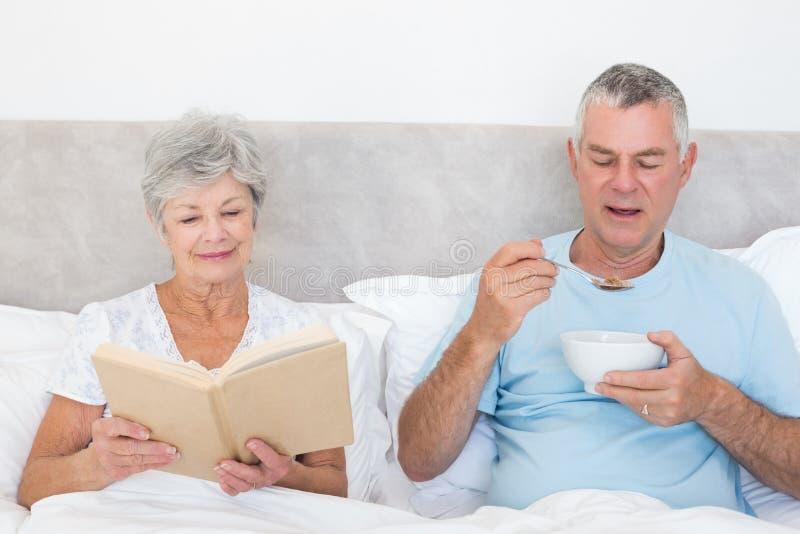 Höga par med boken och den sädes- bunken i säng arkivfoton
