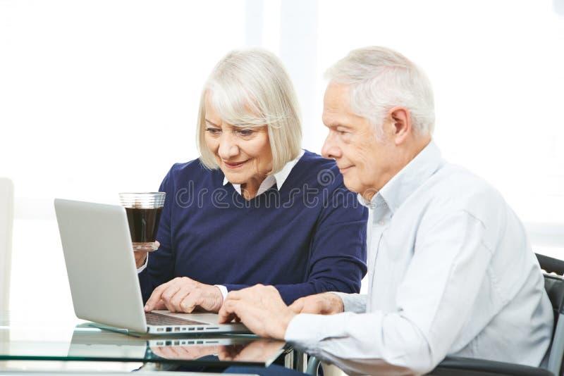 Höga par med datoren som surfar internet royaltyfria bilder