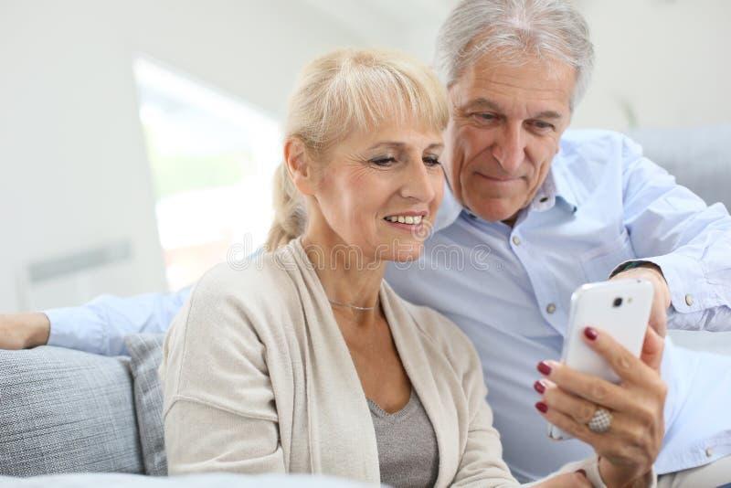 Höga par med den hemmastadda smartphonen royaltyfria bilder