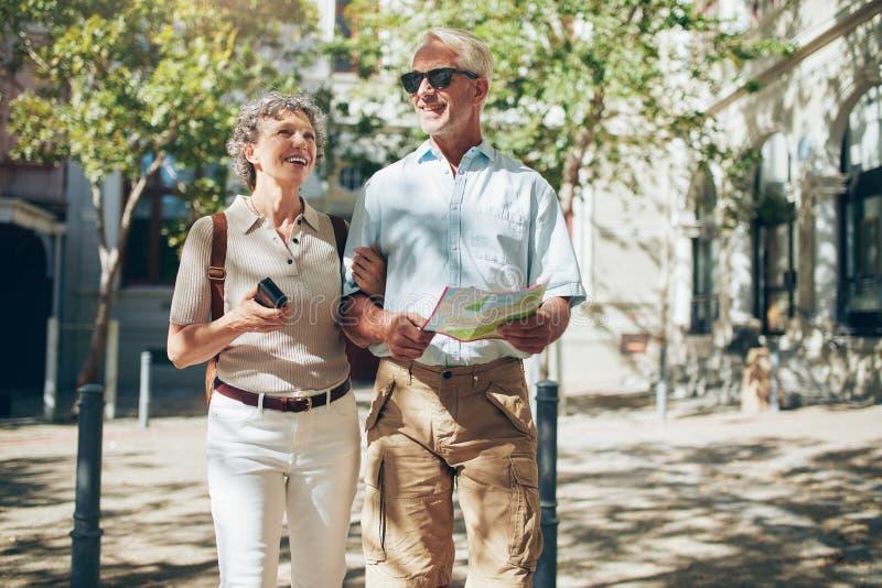 Höga par med en översikt som går i staden royaltyfri foto
