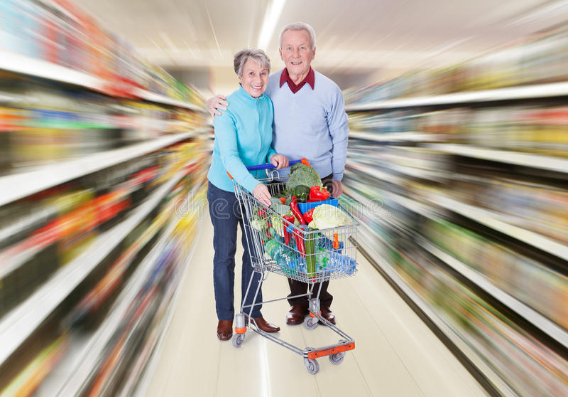 Höga par med en shoppingvagn arkivbild