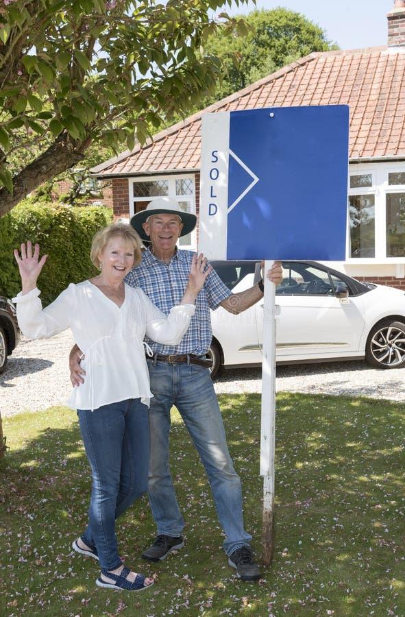 Höga par med ett sålt tecken utanför deras hus royaltyfri fotografi