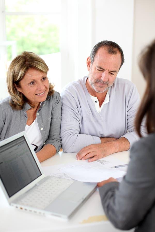 Höga par med fastighetsmäklareläsningavtalet arkivfoton