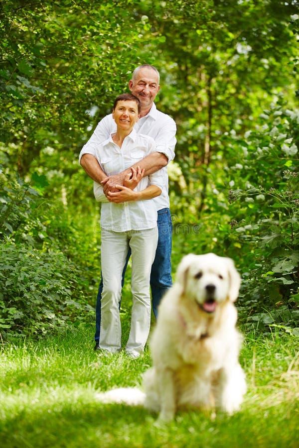 Höga par med hunden som ett husdjur royaltyfri fotografi