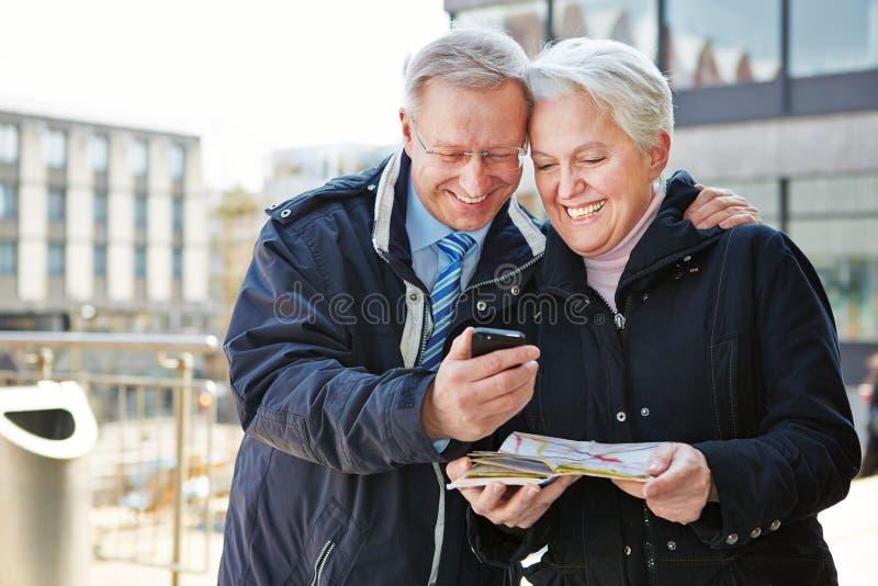 Höga par med stadshandboken app royaltyfri foto