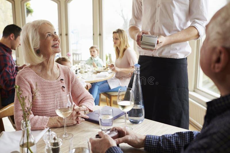 Höga par med uppassaren Paying Bill In Restaurant royaltyfria foton