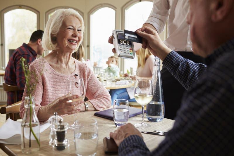 Höga par med uppassaren Paying Bill In Restaurant arkivfoton