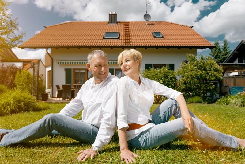 Höga par och deras arbeta i trädgården hem royaltyfri bild