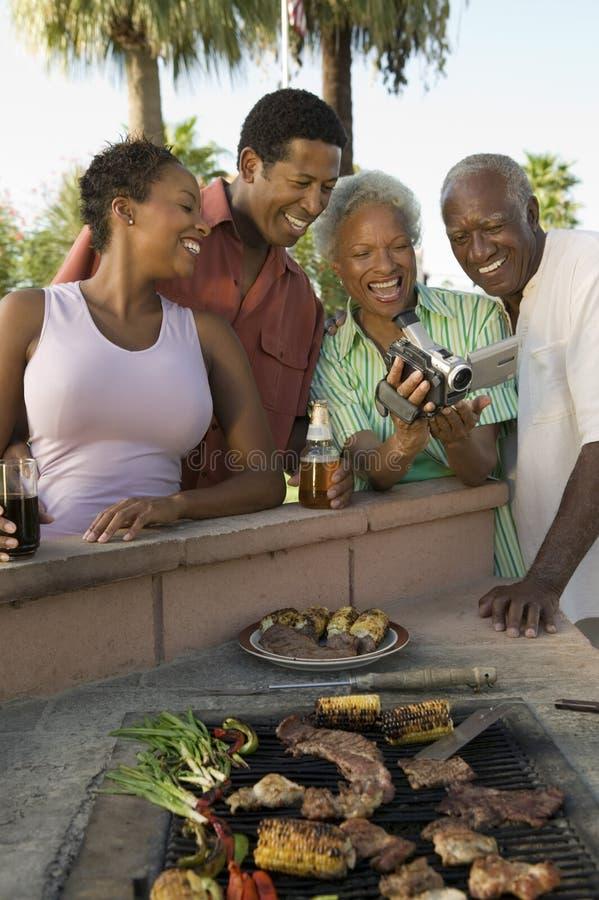 Höga par och mitt--vuxna människan kopplar ihop att se camcorderen på den utomhus- grillfesten. royaltyfri fotografi
