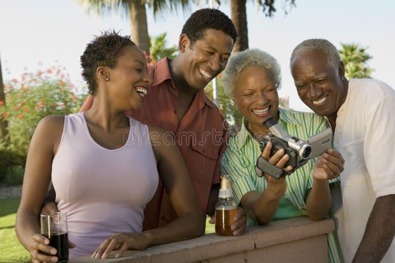 Höga par och mitt--vuxna människan kopplar ihop att se camcorderen utomhus. royaltyfri bild