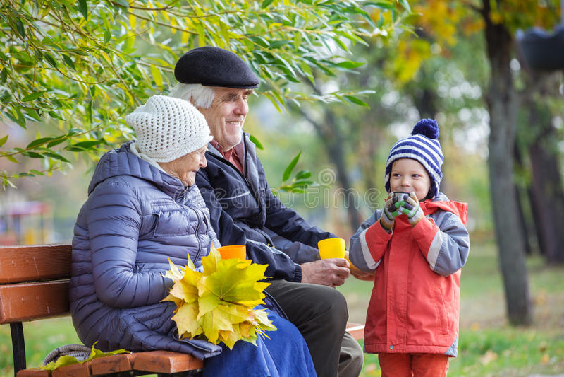 Höga par och sonsonen som dricker varmt te parkerar in royaltyfri bild
