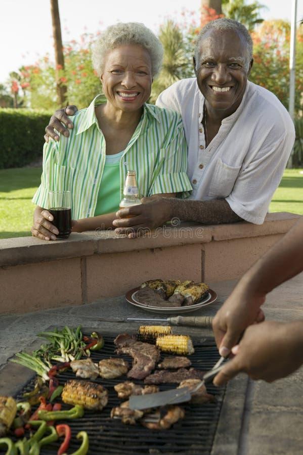 Höga par på den utomhus- grillfestståenden. royaltyfri foto